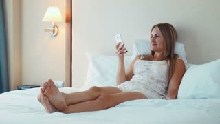 Close up of pretty blonde smiling woman in nighty lying on white pillows and using videochat on smartphone
