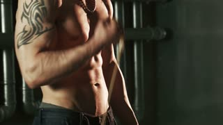 Close-up of tattooed man doing exercise on biceps with expander