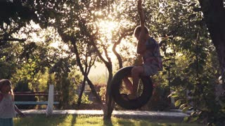 close up, slow motion of happy girl and boy playing at park with tire swing hanging from tree with beautiful sunlight in background