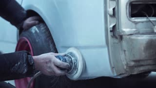 Close up view of auto mechanic using rotary polisher to buff car