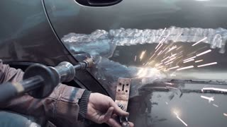 Close up view of special tool scraping paint off a damaged car as used by an auto mechanic