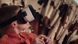 Close view of boy looking through VR headset and gesticulating while sitting on armchair
