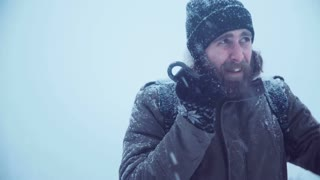 Cold man holding portable radio set and trying to catch a signal in blizzard try to call help, middle 4K shot