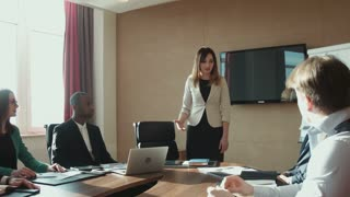 Colleagues applauding businesswoman in office