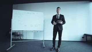 Confident young businessman doing a presentation during a meeting or conference standing alongside a large display chart with a tablet in his hand