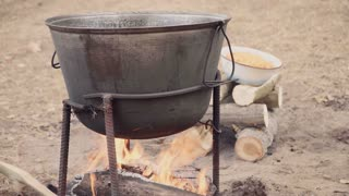 Cooking soup with lamb in a cauldron on a wood stove in the autumn. A man is mixing braised lamb, onion and bell pepper in the cauldron