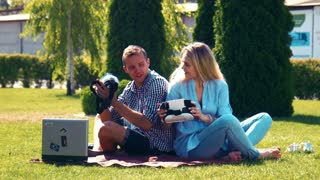 Couple of young woman and man using virtual reality glasses while sitting on blanket in park
