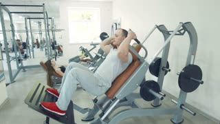 Couple working out in gym. Man in hack machine. woman doing leg press