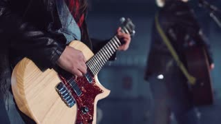 Cropped clip close shot of young incognito woman in leather jacket and ripped jeans playing electric guitar and dancing in empty hall. Camera moving around
