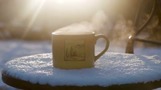 Cup with hot tea against the sun in the winter