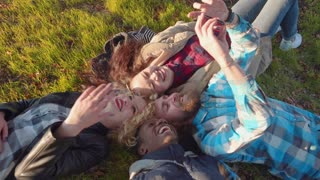 Diverse quartet of friends taking a self portrait with their camera phone while laying down on grass outside. Top view
