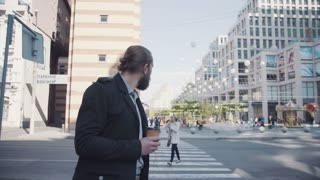 DNIPRO, UKRAINE - OCTOBER 10, 2016: Businessman with beard crossing road with cup of coffee in his hands, using smartphone