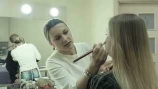 female makeup artist applying makeup on a female client