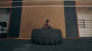 Fit muscular man doing crossfit exercises working out lifting a large rubber tyre in a gym, low angle view in a healthy lifestyle and fitness concept, side view