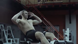 Fit muscular young man doing abdominal crunches to tone and strengthen his abs and muscles in a darkened gym in a health and fitness concept, close up low angle