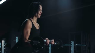 Fit strong young woman lifting weights in a darkened gym, close up of the determined expression on her face and strain and effort as she raises the bar