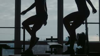 Girl with instructor do fitness exercise together using a step in sport gym