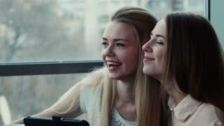 Girlfriends hugging in cafe