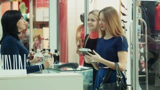 Girls show perfume on the tablet and buy them in shop in mall
