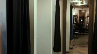 Girls try on dresses in a fitting room
