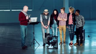 Group of filmmakers using handheld camera gyro stabilizing gimbal. Crew of young men and women watching the director showing cameraman some moves standing in empty studio hall