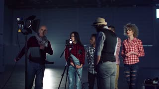 Group of young people filmmakers standing in empty hall with shooting gear and the director showing how to set lighting on actor, switching the studio light stand on