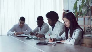 Group or pharmacists sit at conference table wearing lab coats by large window blinds