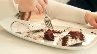 Hands of a young girl holding a fork and eat a sweet dessert or cake at a restaurant or at home