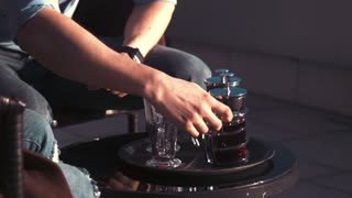 Hands of male which purs tea on the cups in hotel on balcony