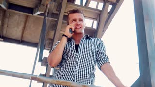 Handsome smiling young man standing on a balcony or lookout chatting on a mobile phone viewed from below
