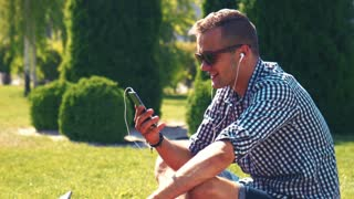 Handsome young man listening to music on his mobile phone sitting outdoors on the grass in a garden or park, or spek with friend via videocall