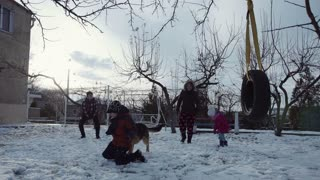 Happy family play with snow in sunny winter day and with sheep-dog. They throw snowballs