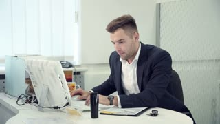 Hardworking businessman typing on a computer as he sits at a table in a modern white office, side view and he has call by the phone there is bad news he is frustrated