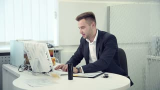 Hardworking businessman typing on a computer as he sits at a table in a modern white office, side view, then he recieved a good news by the phone