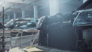 Interior of a panel-beater or body shop with cars being repaired after motor vehicle accidents with tools and parts scattered on the floor