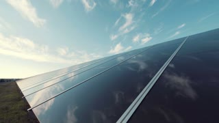 Large solar panel under blue sky with wispy clouds