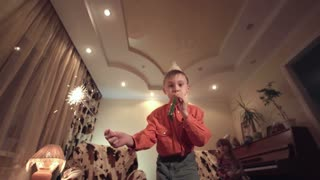 Little boy in Birthday cap holding sparkler and blowing whistle at camera in modern room