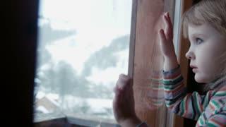 Little cute girl behind window in winter