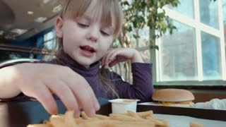 Little girl eating french fries in fast food