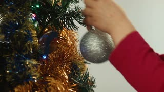 Little girl hangs on a Christmas tree ball