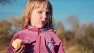 Little girl in a pink jacket and blond hair eating an apple in the park and looks into the camera and smiling