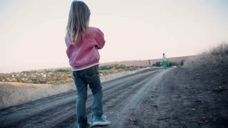 Little girl striding along a country road away from the camera towards her mother standing far off in the distance 4K