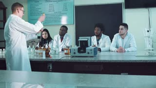 Male lecturer in white coat conducting chemistry experiments in medical classroom with students sitting at desk watching and listening
