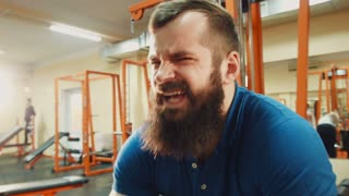 Male with beard lift heavy weight bar in gym