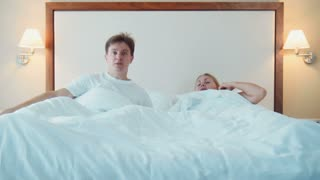 Man and woman woke up in bed and started to scream and look to each other and then run away