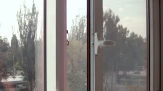 Man closes and opens energy-saving window