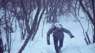 Man covered with snow climbing up to the top of the hill in forest on mountain, wide shot