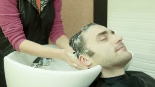 Man in beauty salon washes head