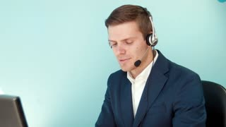 Man in call center smilingly looking at the camera