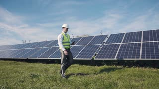 Man in hard hat and yellow reflective vest walking past long row of large solar panels at daytime under blue sky